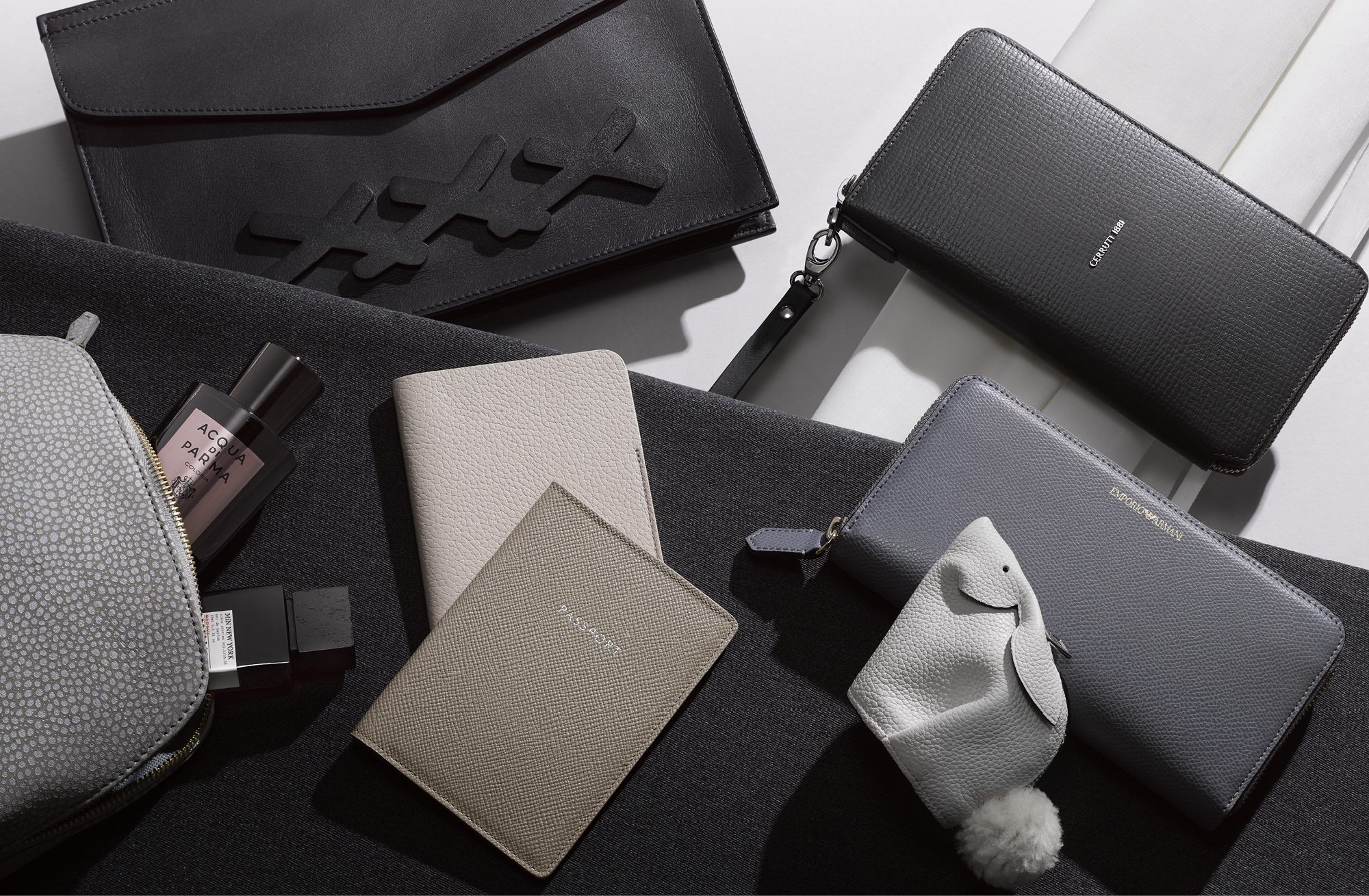 Clockwise from top left: Envelope bag, £1,190, E ZEGNA; leather wallet, £200, CERRUTI; zip wallet, £180, EMPORIO ARMANI; coin pouch, £295, LOEWE; Jet'and Propellor passport sleeves, £165 and £125, GLOBE-TROTTER; cosmetic bag, £135, PADFIELD; Colonia Leather EDC, £179 for 100ml, ACQUA DI PARMA; Scent Stories Barrel EDP, £220 for 75ml, MiN NEW YORK