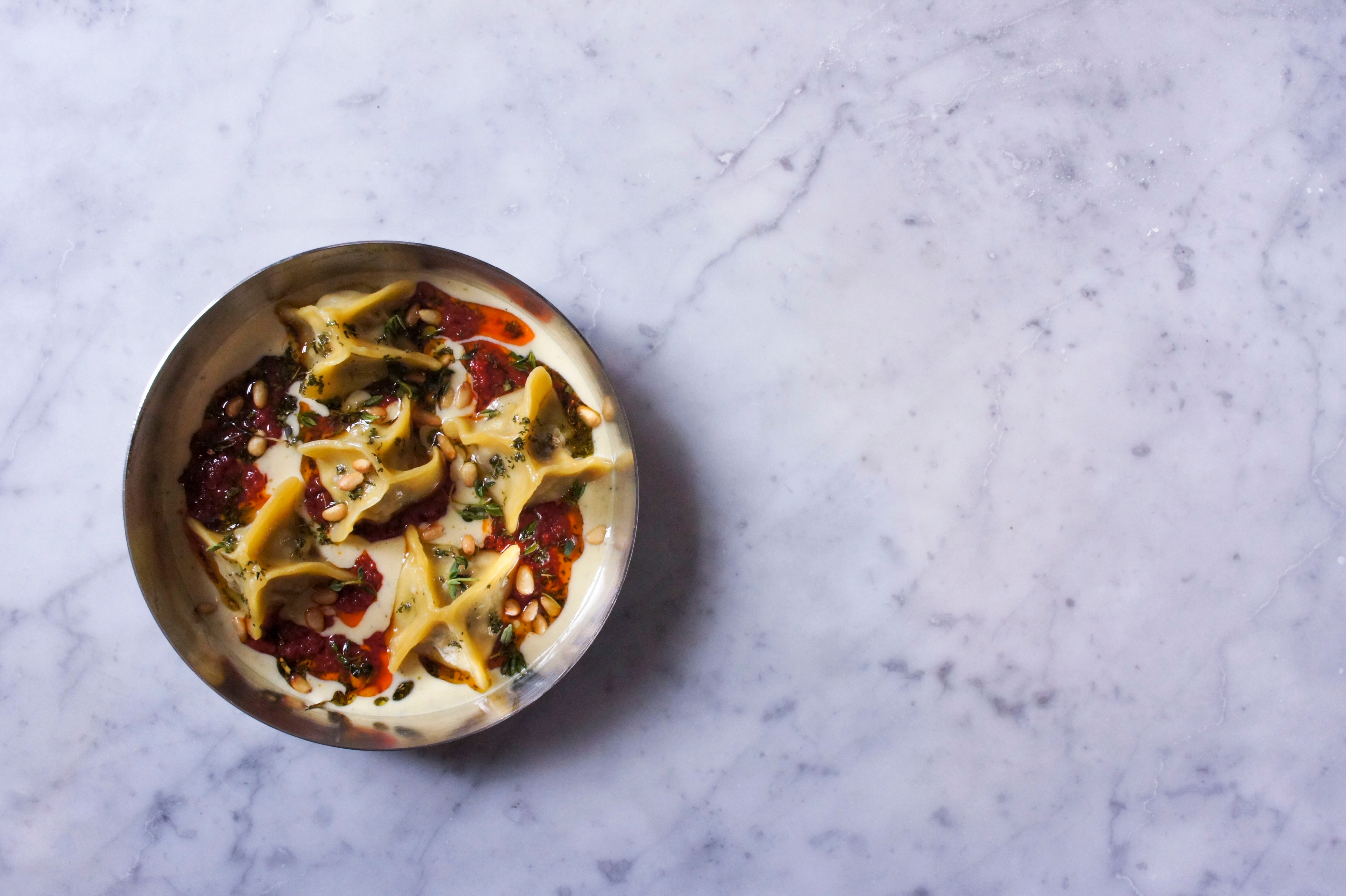 Beef and sour cherry manti, yoghurt sauce, tomato-chilli butter and pine nuts at Kyseri