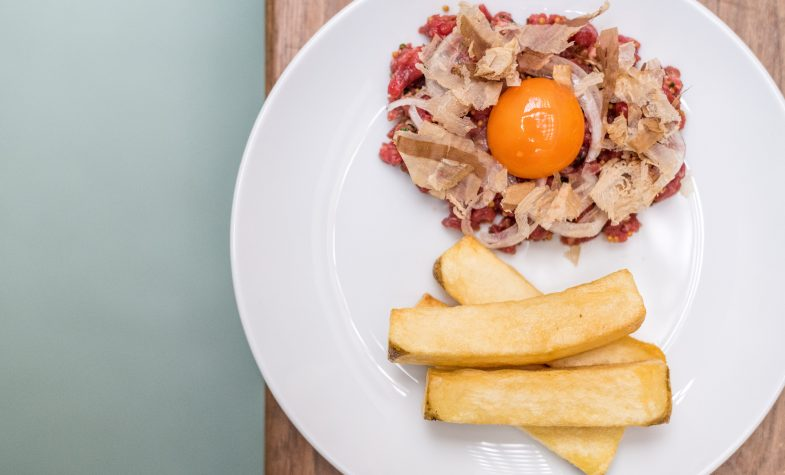 Hereford beef tartar, fermented chilli, prawn oil, egg yolk, bonito, triple-cooked beef fat potato chips at The Laundry